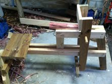 A simple shaving horse I built to make legs for DRG's cedar bench. My feet press the bottom of the lever which pivots on the fulcrum and holds the wood in place as I use a draw knife.